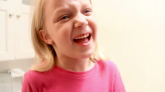 A young girls wobbles and shakes her loose tooth in an effort to remove it - stock footage