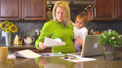 A busy mom tries to multitask with a baby in her arms - stock footage
