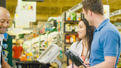 Attractive couple purchase food at grocery store Stock Footage