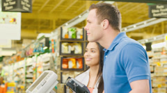 Stock Video Footage of Couple walk through check out counter and exchange smiles with the cashier