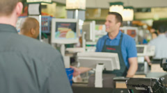 An attractive baby boomer couple go through a checkout line at a grocery store - stock footage