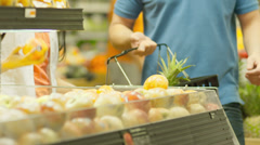 A man starts to play and juggle with fruit as he shops with a woman Stock Footage