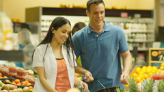 A young couple has fun shopping together in a produce section of a grocery store - stock footage