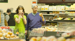 Husband and wife walk through the produce section of a grocery store Stock Footage