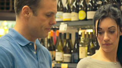 A man uses a phone and a woman looks at a wine selection at a grocery store Stock Footage
