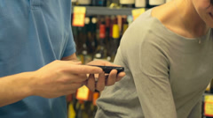 A couple uses a phone to look up different wines as they try to pick one out Stock Footage