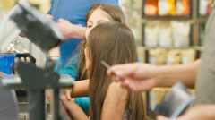 A father and his two daughters go through a check out line at a grocery store - stock footage