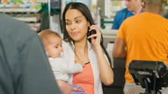 A mother goes through a checkout in a grocery store on the phone and with a baby Stock Footage