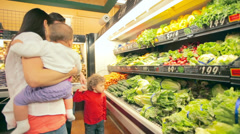A cute young family pick out produce together in a grocery store Stock Footage