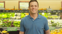 A good looking man stands and smile in front of the camera in a grocery store Stock Footage