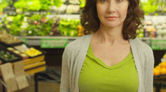 An older woman stands with a blank expression on her face in a grocery store Stock Footage