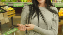 A beautiful young woman smiles for the camera after shopping in a grocery store Stock Footage