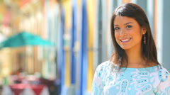 A young Latin woman smiles at the camera and walks away Stock Footage