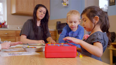Cute preschool kids sit together at a table and play an assortment of games - stock footage