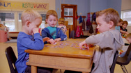 Stock Video Footage of Three preschool boys sit together at a desk and discuss their game of memory