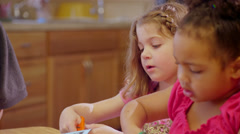 A adorable school child working on an art project with her friends on a table Stock Footage