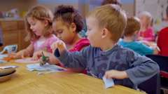 Two cute school children work on a project at a table together during art class Stock Footage
