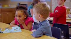 Two cute school children work on a project at a table together during art class - stock footage