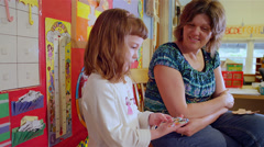 A young school girl talks about her artwork with her teacher in class Stock Footage