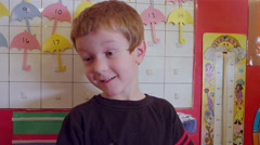 A young boy in school stands in front of the bulletin board in class - stock footage