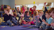 Stock Video Footage of A cute group of preschool students sit together in class and sing a song