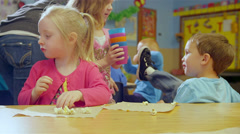 Preschool kids get done eating and pick up the trash and throw it away Stock Footage