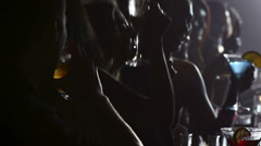 Dark shot of a row of people drinking at a bar Stock Footage