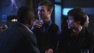 Young men talking at the bar having a drinks and checking out the women Stock Footage