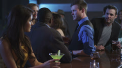 A guy at a bar meets a young woman then flirts with her - stock footage