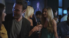 A young people at the bar cheering there drinks, and having a good time - stock footage