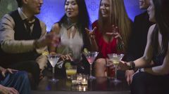 Group of friends sitting at a table in a club cheering there drinks - stock footage