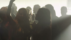 Silhouette in a smokey room of a group of people dancing while at a club - stock footage