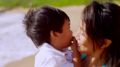 An Asian mom and son hug each other on a beach in Hawaii Stock Footage