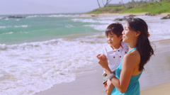 A Asian mom holds her son and looks out in the water on a beach in Hawaii Stock Footage