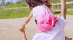 A Asian dad gives his daughter a ride on his shoulders on a beach in Hawaii Stock Footage
