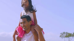 A father gives his daughter a piggy back ride and runs by the water on the beach Stock Footage