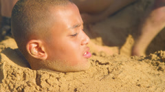 Little kids covering a young boy in sand up to his head on a beach Stock Footage