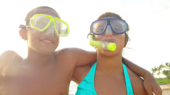 Two kids with swimming mask pose for the camera on a beach in Hawaii - stock footage