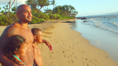 Father and kids gaze at ocean during sunset - stock footage