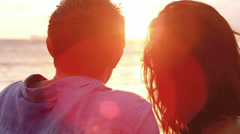 A young couple in love laying on a beach watching the sunset Stock Footage