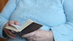 The hands of an old woman are holding prayer book Stock Footage