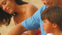 A young family watch their kids while smiling and laughing on a beach in Hawaii - stock footage