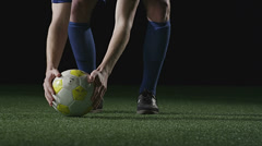 A soccer play sets the ball down and then steps back to kick it - stock footage