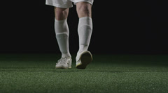 A soccer play sets down the ball and then gives it a big kick - stock footage
