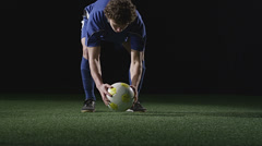 A soccer player places a ball and then kicks the ball very hard - stock footage