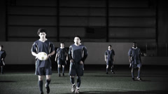 Soccer players stand at midfield and pass the ball to get the game underway Stock Footage