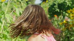 A girl stands and then turns around and runs through the garden thats behind her Stock Footage