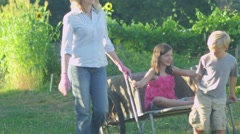 A girl sits in a wheelbarrow while her brother pulls her along in a garden Stock Footage