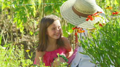 A cute little girl sits smiling while her grandma shows her how to pant flowers Stock Footage