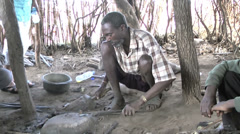 Tanzanian smith in Masai village melting metal, Kigali Stock Footage